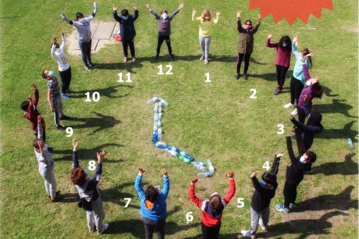 studenti per mano in cerchio in piedi sul prato con lancette e orologio creato nel mezzo, fotografia dall'alto