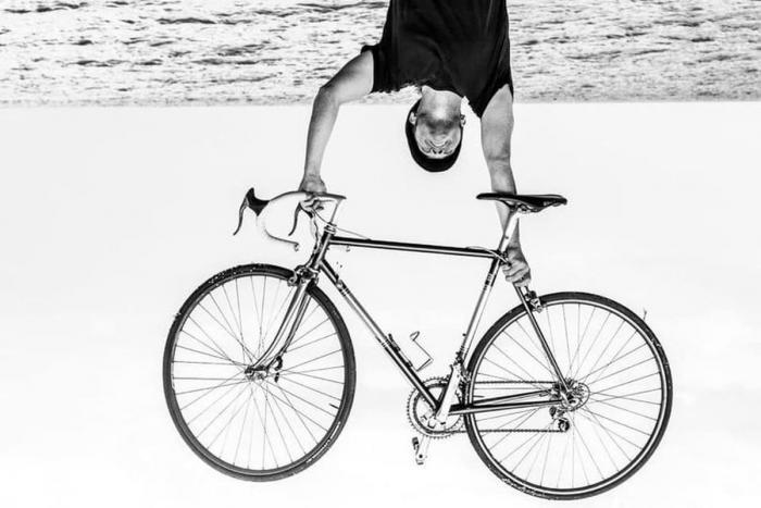 fotografia b/n uomo che solleva in alto bicicletta da corsa