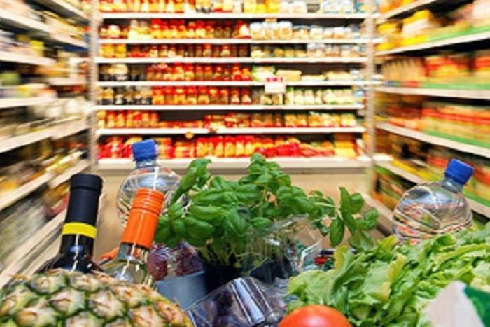 carrello spesa ricolmo tra gli scaffali del supermercato