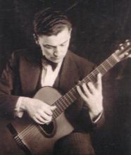 Maccaferri in abito gessato seduto che suona una delle sue chitarre